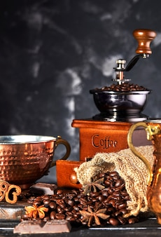 Old manual coffee grinder with coffee beans and a cup of coffee on a gray . coffee