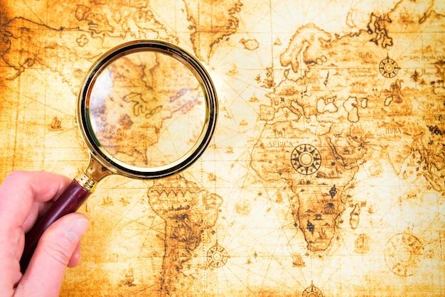 Старая карта и увеличительное стекло в руке исследовали его. винтаж путешествия фон