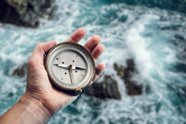 Old marine compass in the hand on the sea background