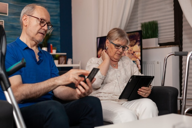 Old married people using digital devices and sitting together
