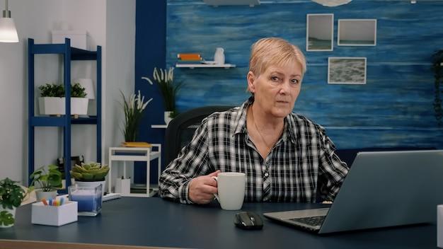 Старая зрелая бизнесвумен сидит на рабочем месте и набирает текст на ноутбуке, пьет кофе из дома
