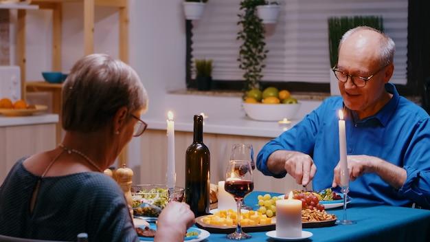 현대 부엌에 있는 테이블에 앉아 낭만적인 저녁 식사를 하는 노부부. 쾌활한 노인들이 이야기하고 식사를 즐기고 식당에서 기념일을 축하합니다.