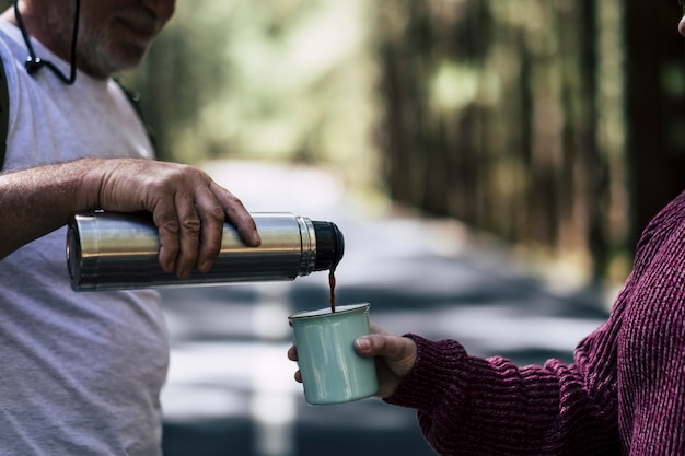 Пожилой зрелый мужчина угостит женщину чашкой горячего кофе во время путешествия посреди леса для альтернативного образа жизни, связанного с охотой к путешествиям, для диких людей без возрастных ограничений, наслаждайтесь исследованиями и