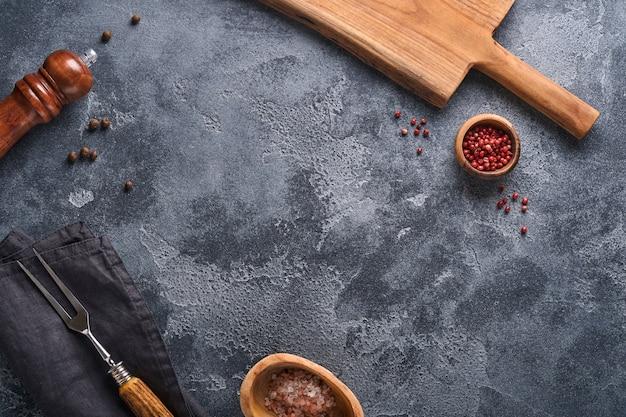古い灰色のコンクリートの背景に古い肉のフォーク、黒いプレート、黒胡椒と黒胡椒とスパイスミル。料理の背景とモックアップ。