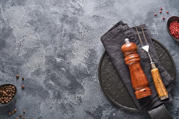 오래 된 회색 콘크리트 배경에 오래 된 고기 포크, 검은 접시, 검은 후추, 검은 후추와 향신료 밀. 음식 요리 배경과 조롱.