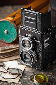 Old mechanical photo camera on an old background