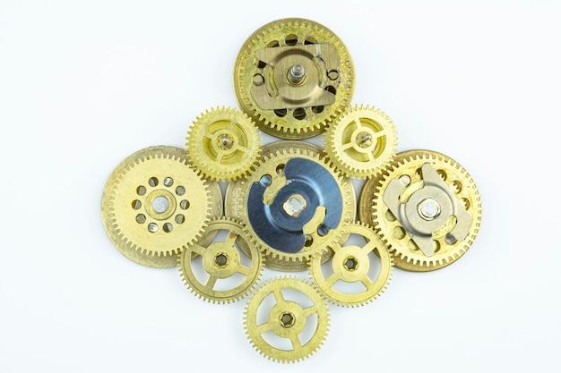 Старый механизм собран из бронзовых зубчатых колес, изолированных на белом фоне.