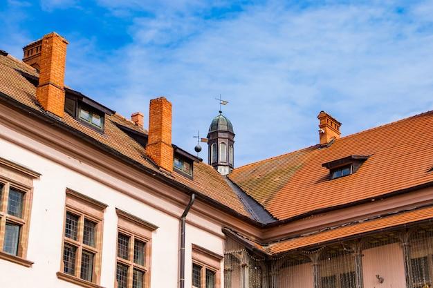 青い空を背景にした古い中世の建物。古代建築。赤い屋根瓦の家。