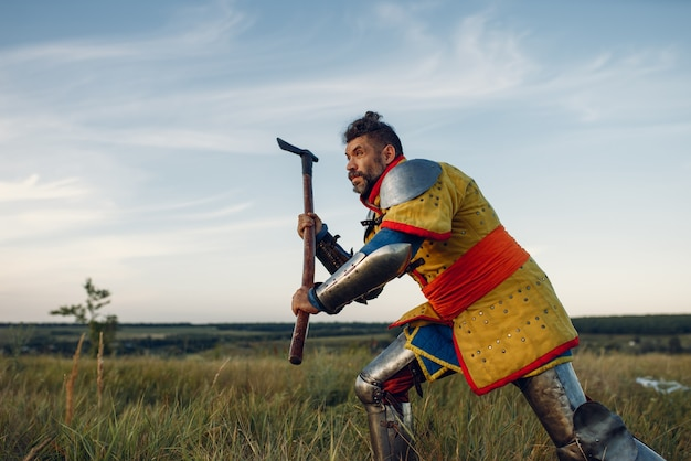 Old medieval knight in armor holds axe, great tournament. armored ancient warrior in armour posing in the field