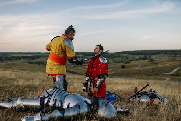 Old medieval knight in armor prepares to cut off head, great battle. armored ancient warrior in armour posing in the field