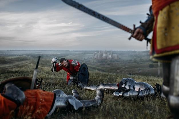 Старый средневековый рыцарь в доспехах смотрит на мертвых после великой битвы. бронированный древний воин в доспехах позирует в поле