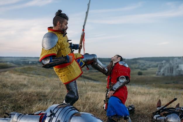 Старый средневековый рыцарь в доспехах готовится отрубить голову, великое сражение. бронированный древний воин в доспехах позирует в поле