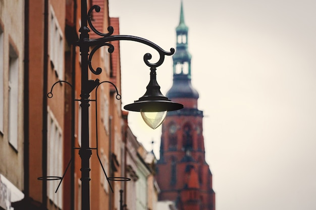 Old medieval street lamp and church on background
