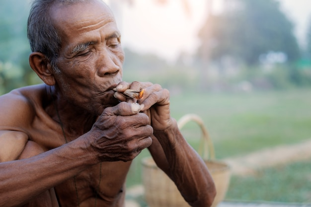 Old men are smoking cigarettes.