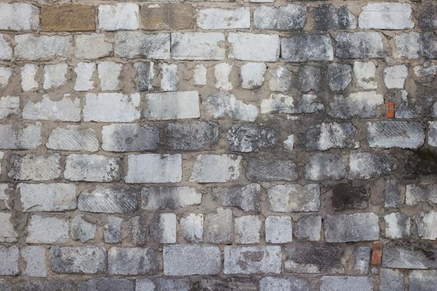 Старая грязная белая каменная стена с прессформой, горизонтальной текстурой. грубая стена