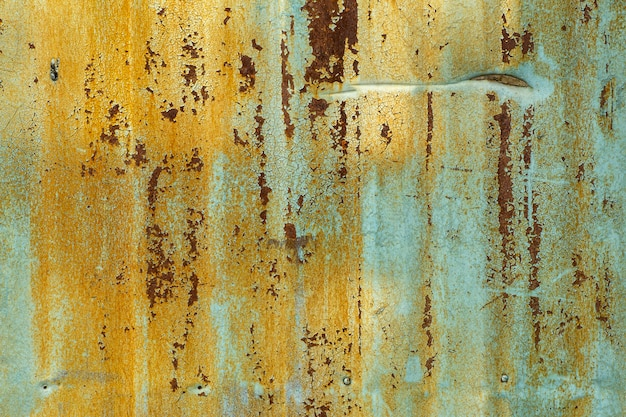 오래 된 금속 배경입니다. 녹슨 금속 표면에 오래 된 말린 된 녹색 노란색 페인트의 질감
