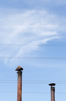 Old metal chimney pipes on a background of blue sky and wires