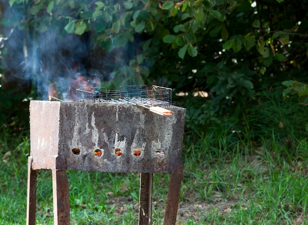 Old metal dirty brazier while cooking barbecue in the forest, eastern europe