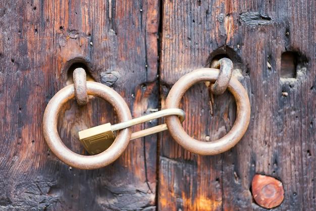 Старая металлическая дверная ручка молотка на грубом деревянном фоне