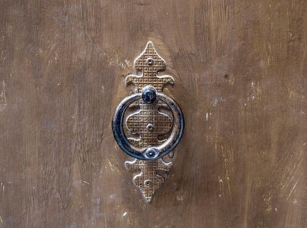 An old metal door handle on old wooden door