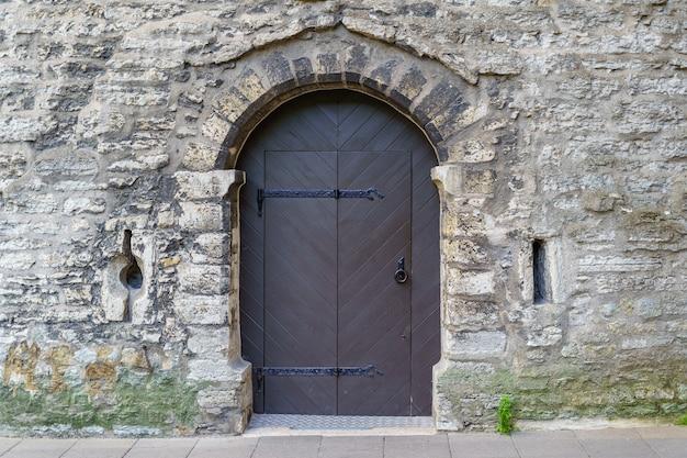 Old metal door in medieval castle facade.