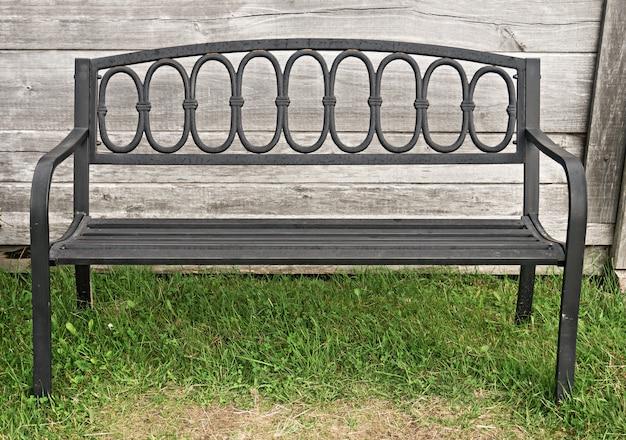 Старая металлическая кованая скамейка у деревянной стены