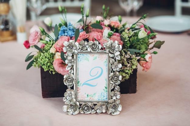 «старая металлическая рамка и цветы на столе»