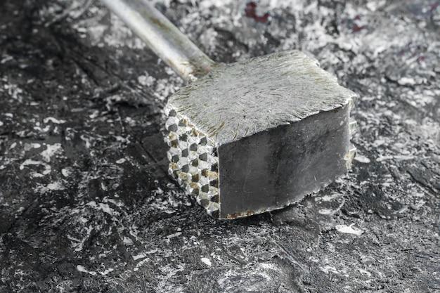 古い金属製のキッチンハンマーは灰色のコンクリートの背景にクローズアップ