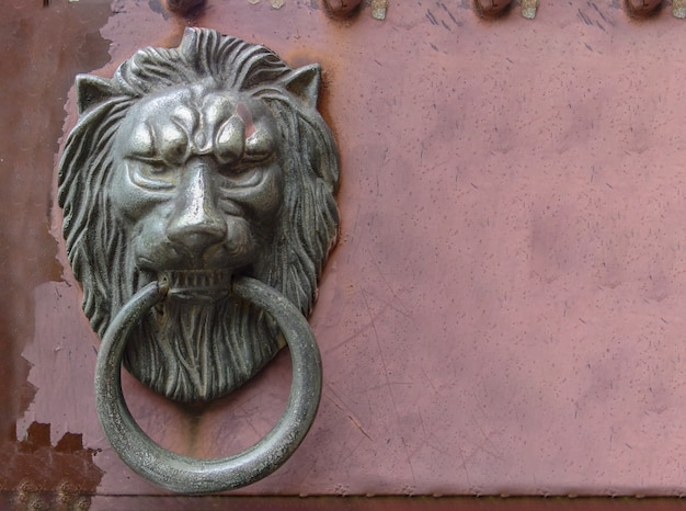 Old metal lion knock door on grunge red wall background.