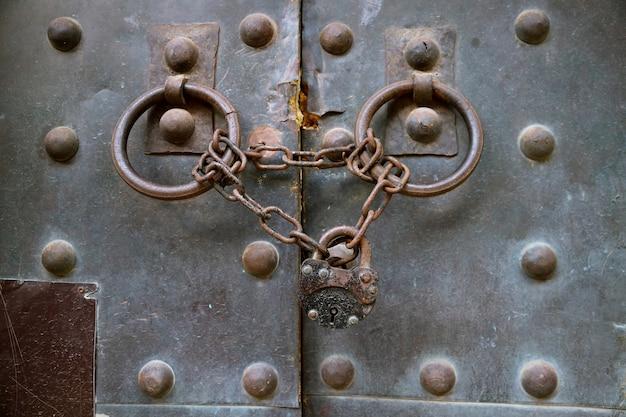 Old metal medieval door with chain lock
