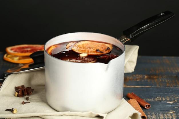 Старая металлическая сковорода вкусного глинтвейна на деревянном столе