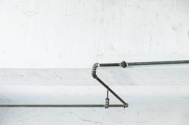 Старая труба металла на белой стене.