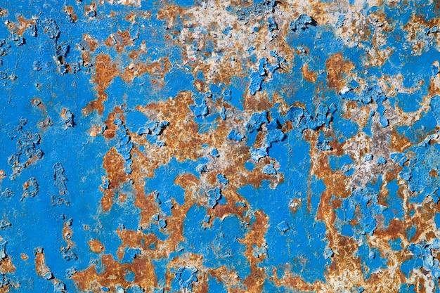 파란색 페인트가 있는 오래된 금속 녹슨 벽