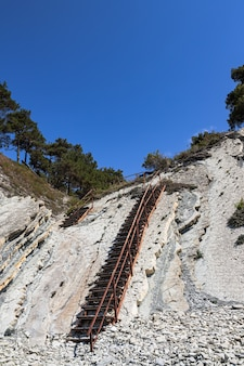 An old metal staircase and massive white rocks on a wild beach.