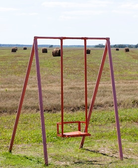 Old metal swing on the field, cloudy weather in autumn or late summer