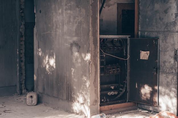 廃墟の崩れかけた建物にある古い金属製配電盤
