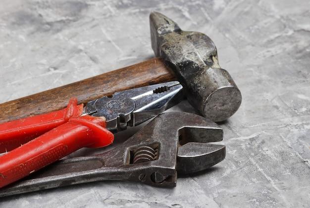 Старые металлические инструменты на серой бетонной поверхности