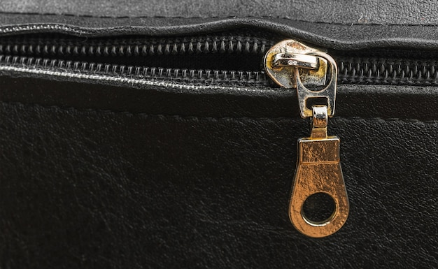Old metal zipper bag close-up, zip on a leather bag, copy space photo