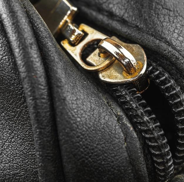 Старая металлическая сумка на молнии на кожаном винтажном материале, крупный план фоновой фотографии