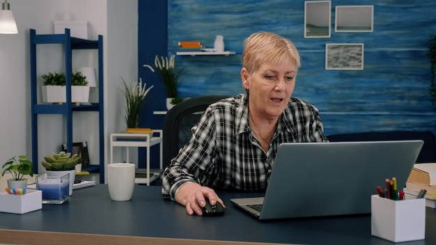 Old middle aged businesswoman working at laptop typing financial data
