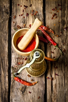 Old mill and mortar with ground red chili pepper on wooden table. top view