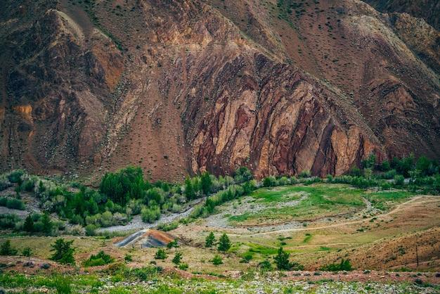 여러 가지 빛깔의 언덕과 찰흙 산 벽 사이의 작은 강과 푸른 나무가있는 계곡에서 오래된 광산.