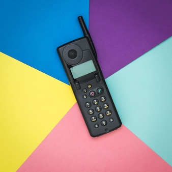 Old mobile phone on a surface of five colors