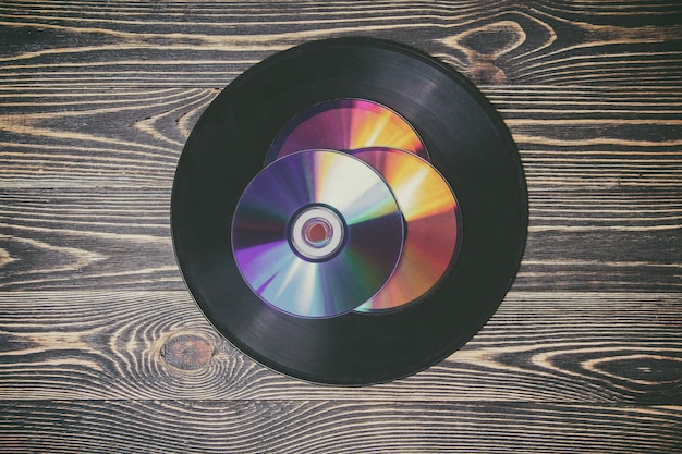 Old and morden audio disks on the wooden table