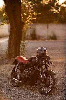 屋外でヘルメットと古いオートバイ