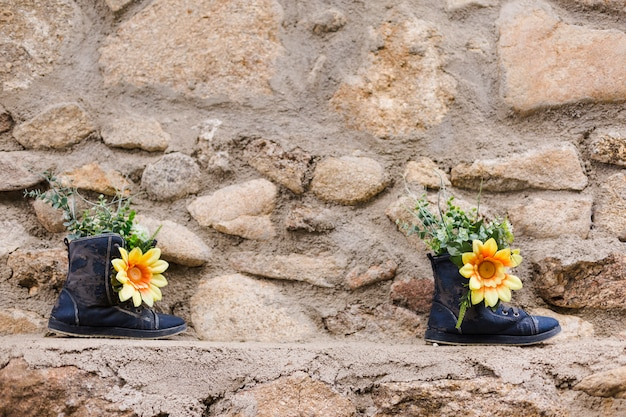 Old mountain boots used as flower pots. decoration outdoors over a stone wall.
