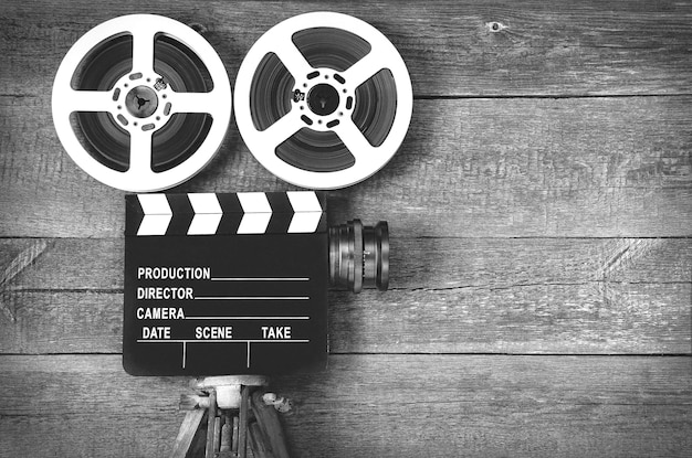 Old movie camera, consisting of a tripod, lens, film reels and clapperboards. black and white photo.
