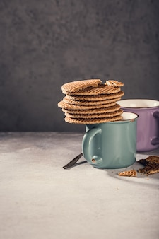コピースペースのある灰色の表面にチョコレートミルクと伝統的なオランダのクッキーストロープワッフルが入った古いマグカップ。レトロなスタイルのトーン
