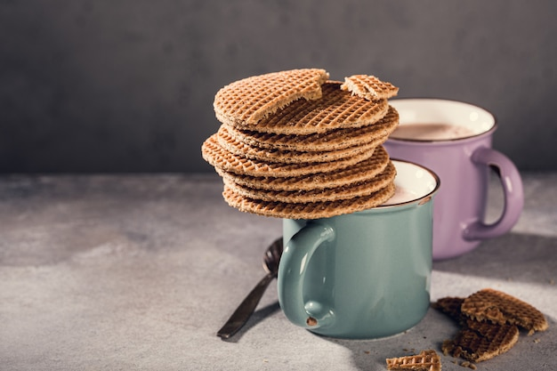 Old mug with chocolate milk and traditional dutch cookies stroopwafels on gray surface with copy space. retro style toned