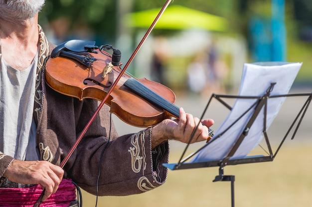 거리의 악보대 근처에서 바이올린을 든 늙은 음악가_